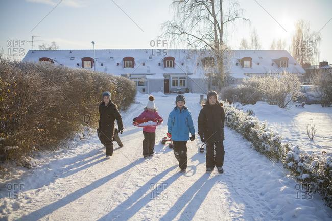 Sweden, Vastergotland, Lerum, Portrait of three boys and girl walking along snowy driveway, dragging sleds