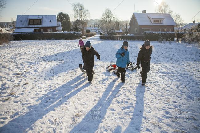 Sweden, Vastergotland, Lerum, Portrait of three boys running along snowy road, dragging sleds