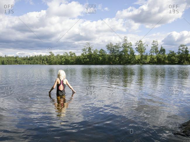 Sweden, Vastergotland, Lake Ommern, Girl walking away into calm lake