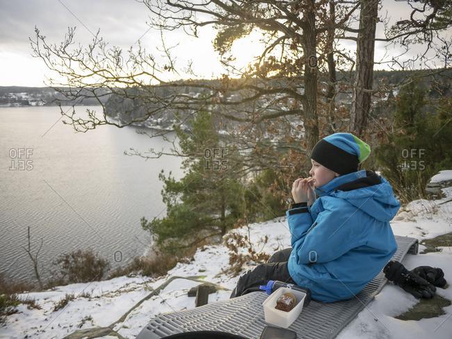 Sweden, Vastergotland, Lerum, Lake Aspen, Portrait of boy sitting on snowy lakeshore, eating