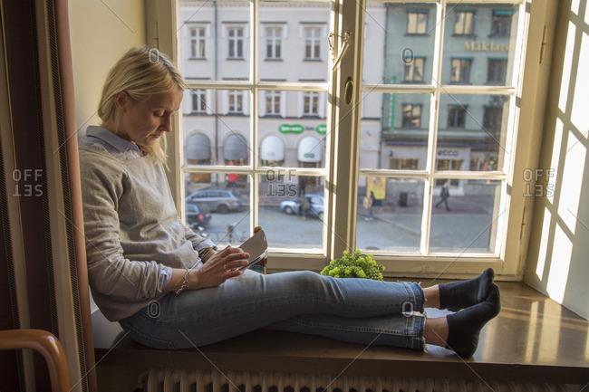 Sweden, Skane, Helsingborg, Woman sitting on window sill with smart phone