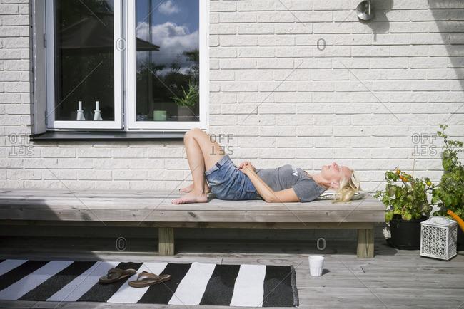 Sweden, Vastergotland, Lerum, Mature woman lying on bench