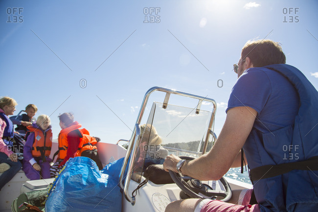 Sweden, Swedish West Coast, Holland, Kungsbackafjorden, Man with kids (6-7, 8-9, 10-11) on motor boat