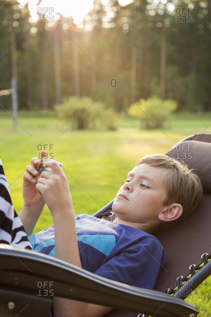 Sweden, Narke, Kilsbergen, Boy using smart phone