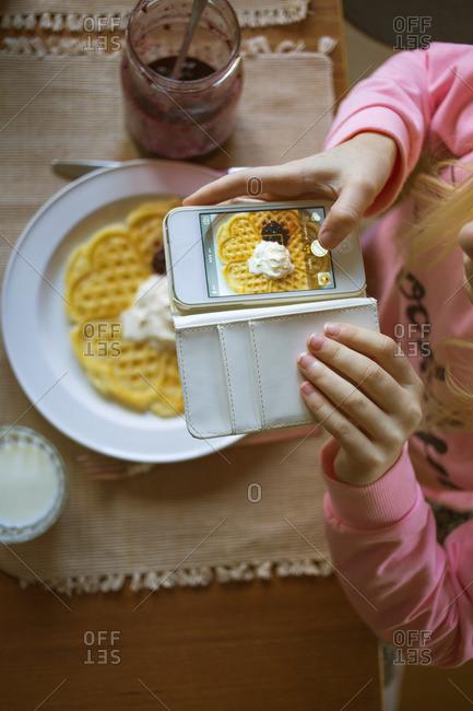 Sweden, Vastergotland, Girl photographing Belgian waffle