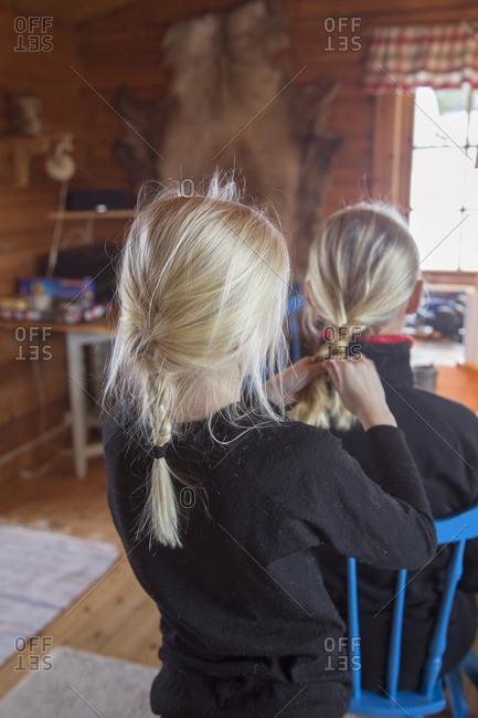 Norway, Girl tying mother's hair