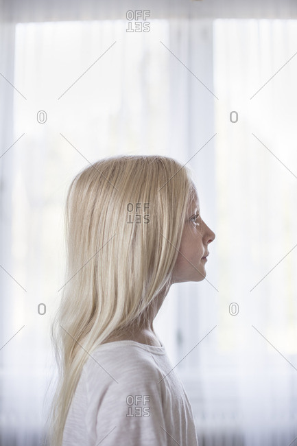 Sweden, Side view of blonde girl in front of white curtains