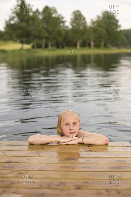 Sweden, Smaland, Braarpasjon, Portrait of girl in lake with hands on chin