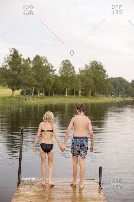 Sweden, Smaland, Braarpasjon, Girl and boy standing on edge of jetty