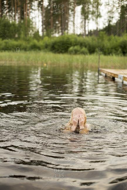 Sweden, Smaland, Braarpasjon, Girl in lake drying off eyes with hands