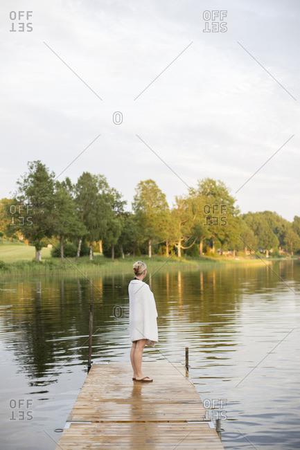 Sweden, Smaland, Braarpasjon, Mature woman wrapped in towel standing on jetty