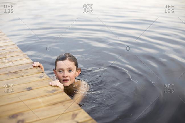 Sweden, Smaland, Braarpasjon, Portrait of boy in lake touching wooden jetty