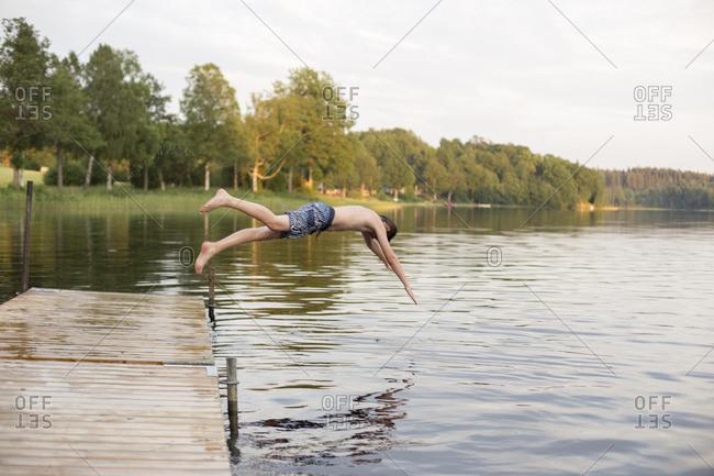 Sweden, Smaland, Braarpasjon, Boy jumping into lake from jetty