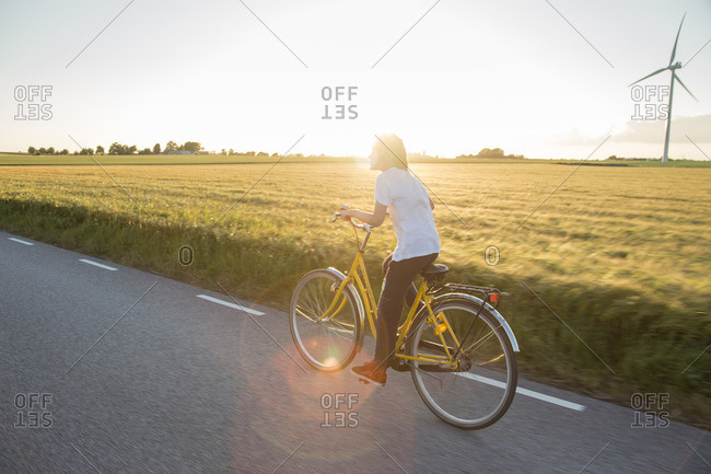 Sweden, Skane, Soderslatt, Beddinge, Boy riding bicycle on sunny day