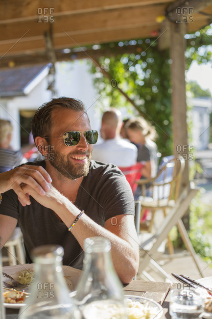 Sweden, Skane, Mature man in sunglasses eating lunch