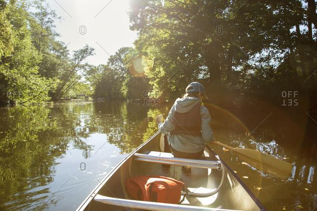 Sweden, Vastergotland, Lerum, Savean, Boy in baseball cap sitting in canoe
