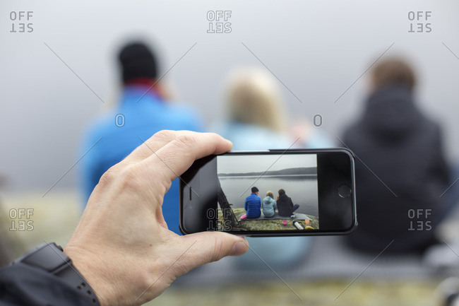 Sweden, Vastergotland, Lerum, Harskogen, Harsjon, Man taking picture of woman with two sons (10-11, 12-13) with smartphone
