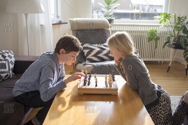 Sweden, Boy and girl playing chess in living room