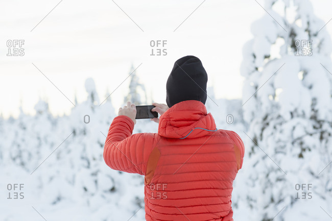 Sweden, Lapland, Gallivare, Mid-adult man photographing forest in winter