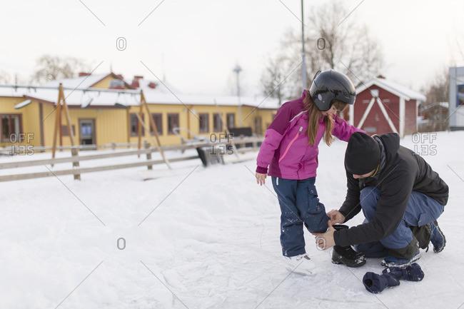 Sweden, Vasterbotten, Umea, Mother helping daughter with ice skates