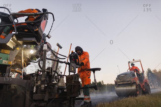 Sweden, Narke, Two manual workers repairing road