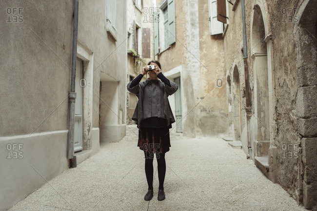 France, Languedoc-Roussillon, Sauve, Young woman photographing in old town