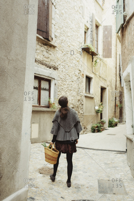 France, Languedoc-Roussillon, Sauve, Young woman walking in old town
