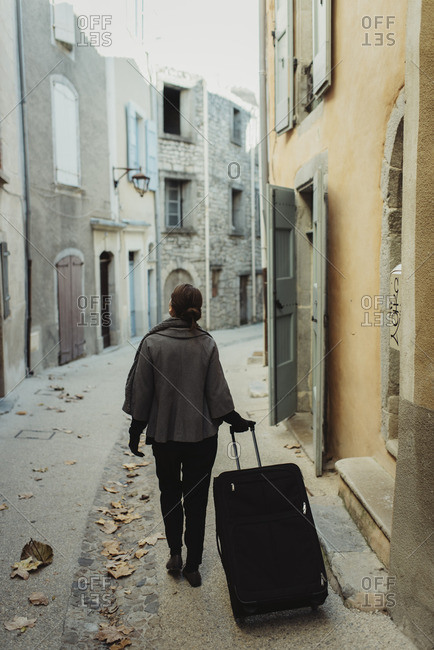 France, Languedoc-Roussillon, Sauve, Young woman walking with luggage in old town