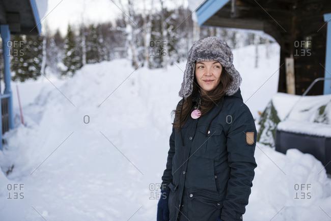 Sweden, Lapland, Hemavan, Young woman wearing parka and fur hat in winter
