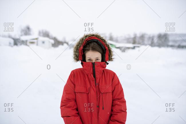 Sweden, Lapland, Hemavan, Portrait of young woman wearing red parka in winter