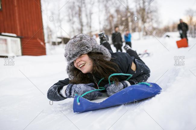 Sweden, Lapland, Hemavan, Young woman sliding on toboggan in winter