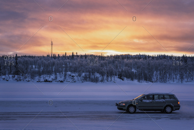 Sweden, Lapland, Hemavan, Car on dirt road covered with snow at sunset