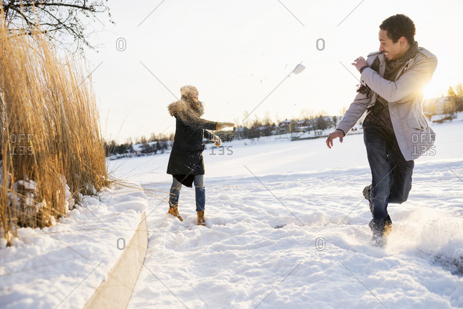Sweden, Vasterbotten, Umea, Young couple enjoying snowball fight