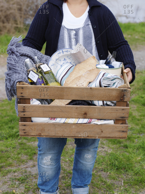 Sweden, Woman carrying big wooden picnic box