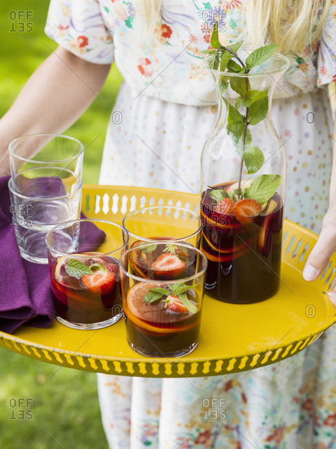 Sweden, Skane, Woman holding yellow tray with sangria drinks
