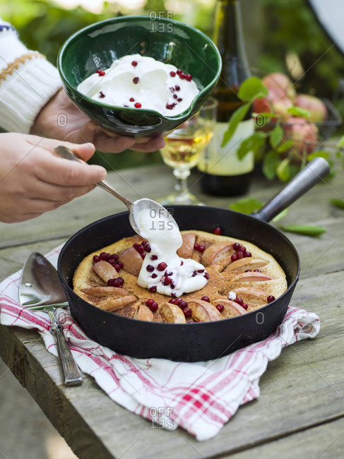 Sweden, Woman pouring cream on apple cake