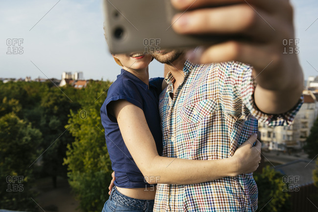 Germany, Berlin, Young couple hugging and taking selfie with smart phone