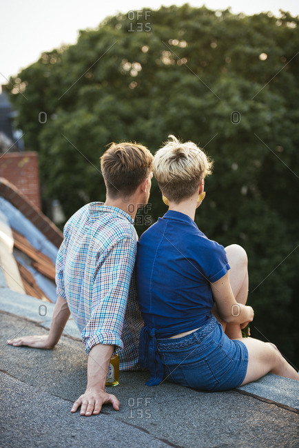 Germany, Berlin, Young couple sitting on rooftop with beer