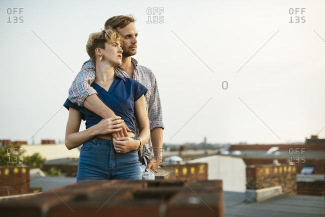 Germany, Berlin, Young couple standing on rooftop against sky