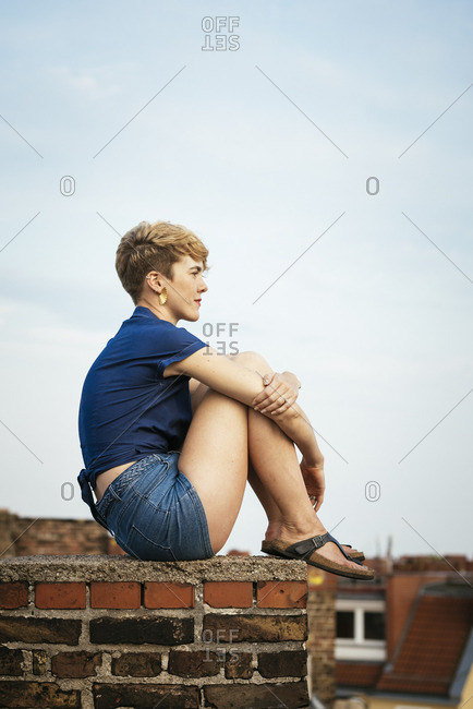 Germany, Berlin, Young blonde woman sitting on rooftop at sunset
