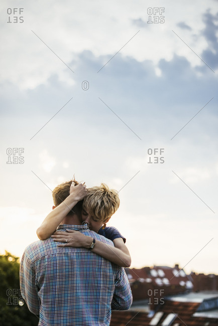 Germany, Berlin, Young couple hugging on rooftop at sunset