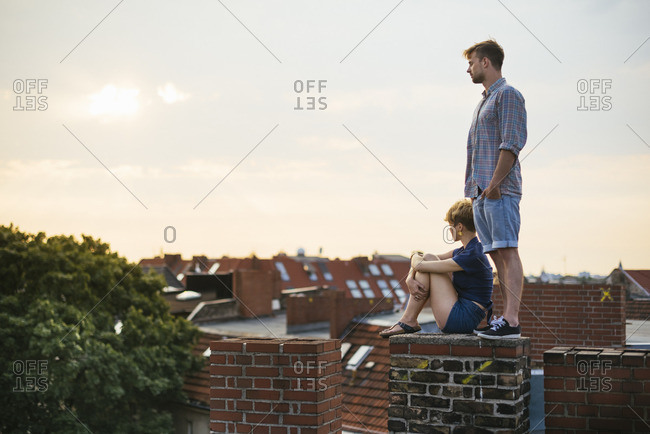 Germany, Berlin, Young couple on rooftop against sky