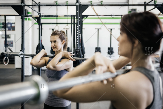 Germany, Two young women weightlifting in gym
