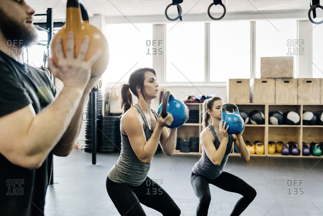 Germany, Young women and man cross training with kettlebells in gym
