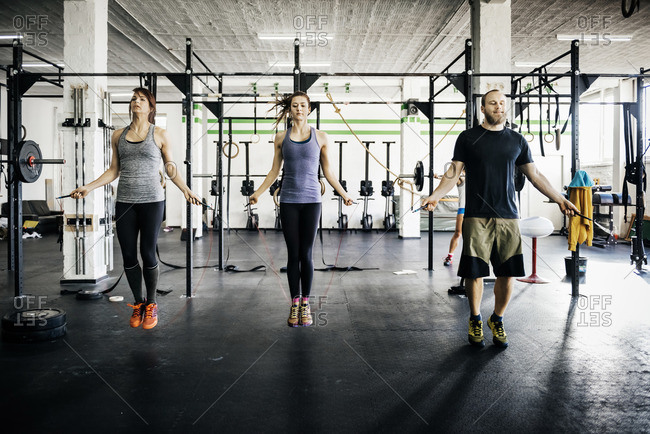 Germany, Young women and man skipping rope in gym