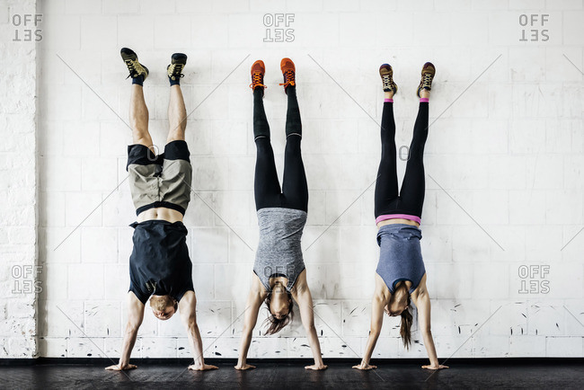 Germany, Young women and man practicing handstand in gym