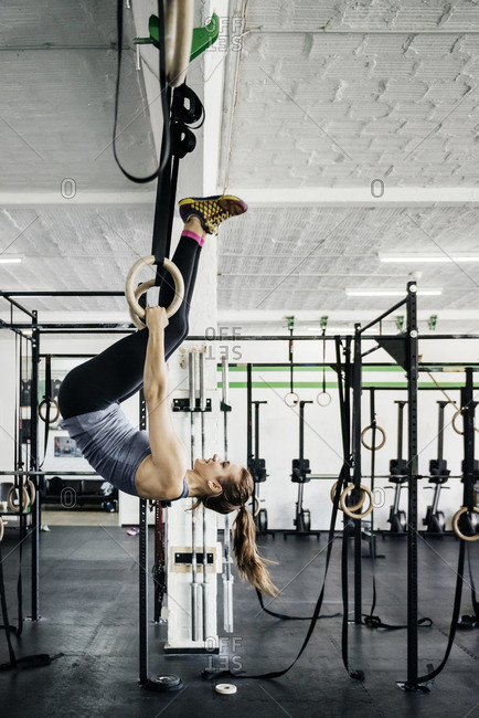 Germany, Young woman training on gymnastic rings