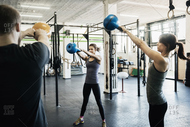 Germany, Young women and man swinging kettlebells in gym