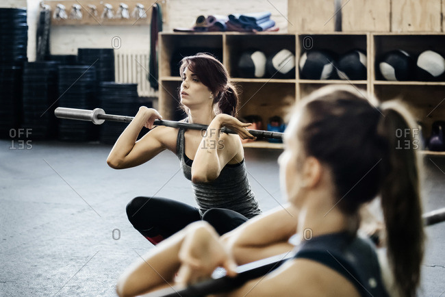 Germany, Two young women training with barbells in gym