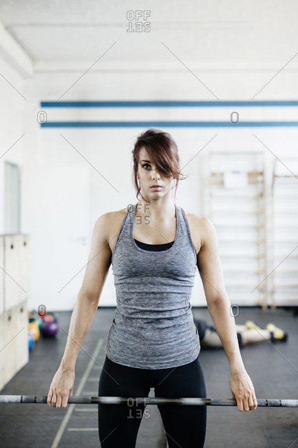 Germany, Young woman training with barbell in gym